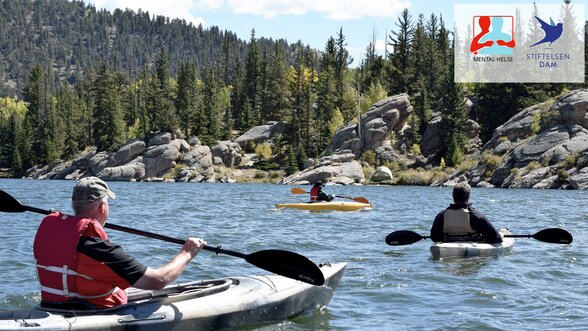 Three men riding kayaks on body of water 1497587